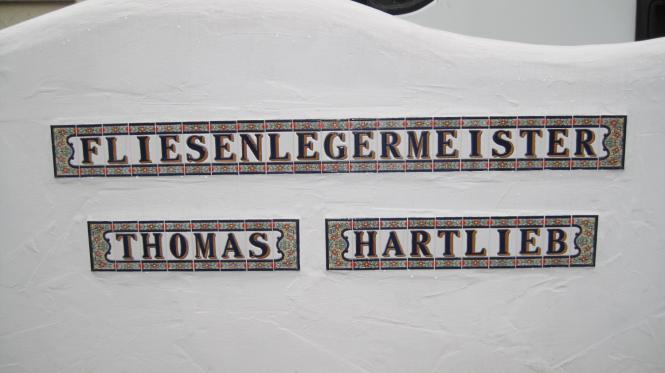 Außenmauer mit Schriftzug und Mosaikbild